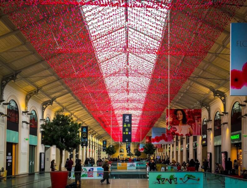 Projet Kenzo centre commercial plafond fleuri sur filet pare-ballons