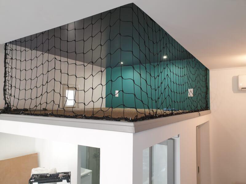 Protection originale d'une mezzanine avec un filet garde-corps noir