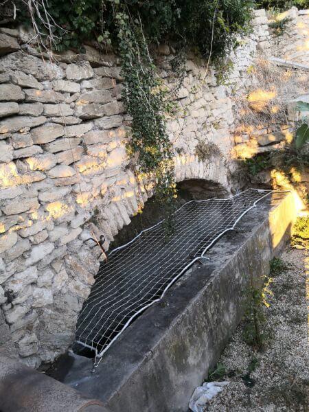 Filet de sécurité installé sur un bassin en pierre