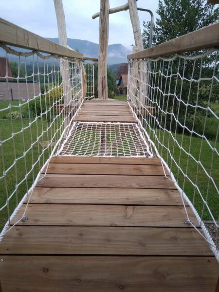 Pont en bois pour enfant sécurisé par un filet de protection garde-corps