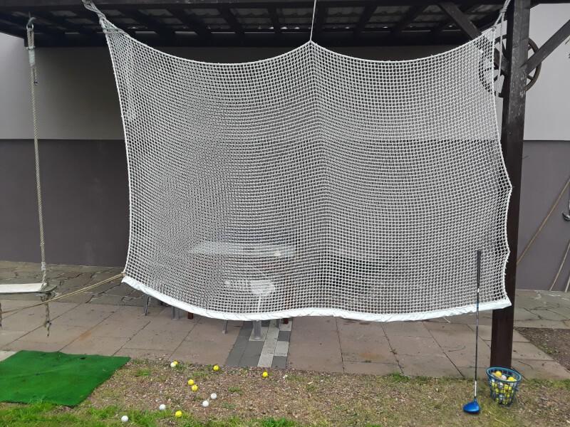 Un terrain de golf à la maison avec un filet de practice pour tir à bout portant