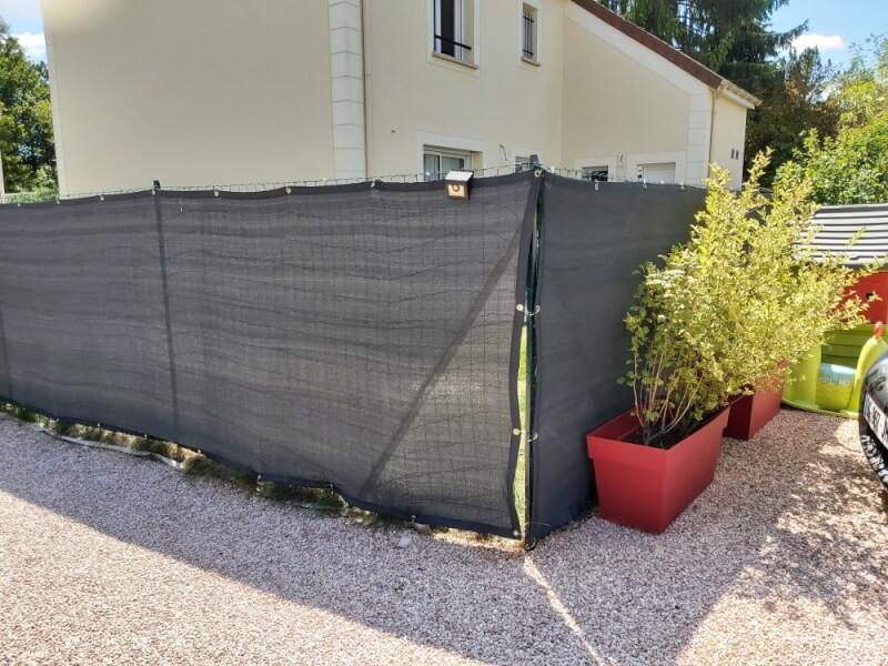 Installation d'un filet brise-vue gris dans un jardin