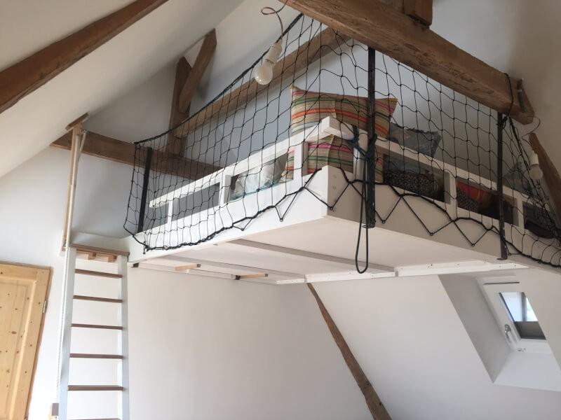 Espace détente en mezzanine protégé par un filet noir