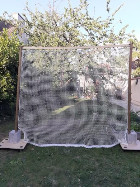Filet de practice de golf doublé et monté sur un support mobile dans un jardin