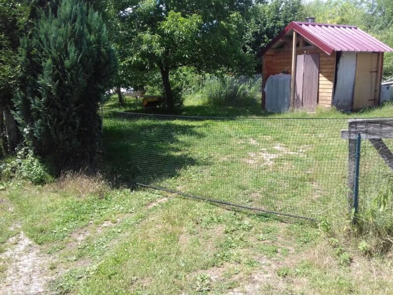 Filet de volière utilisé comme clôture et portail d'entrée sur une propriété privée