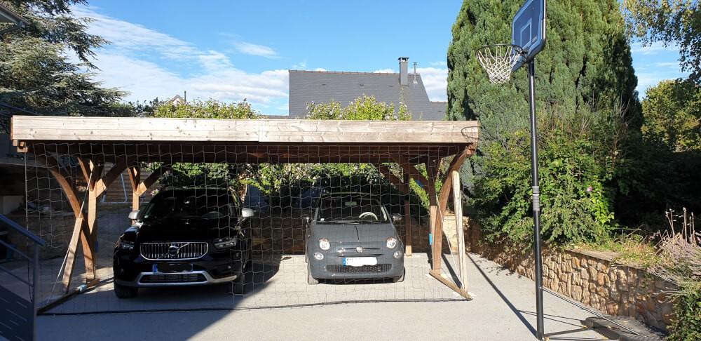 Filet pare-ballons autour d'un carport pour protéger les voitures