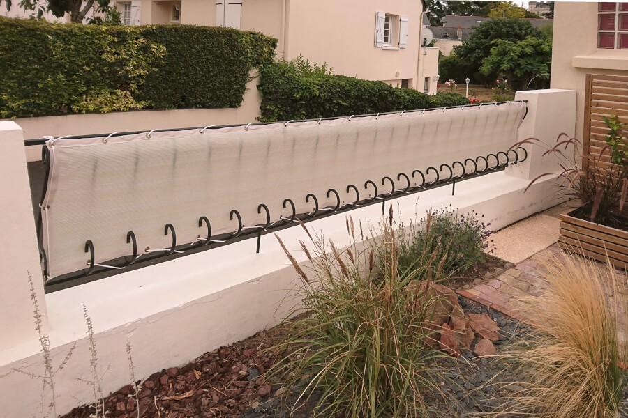 Filet brise-vue sur clôture en fer forgé