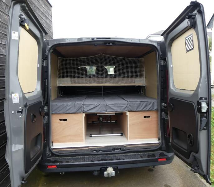 Installation du filet de sécurité dans le camion aménagé pour finaliser le lit enfant.