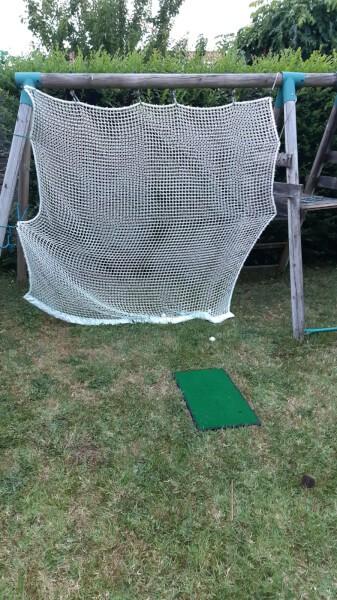 Balançoire convertie en terrain de golf avec un filet de practice doublé