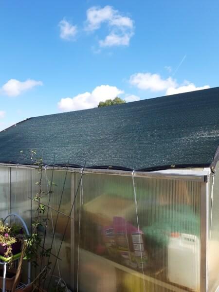 Filet d'ombrage anti-chaleur installé sur abri de jardin
