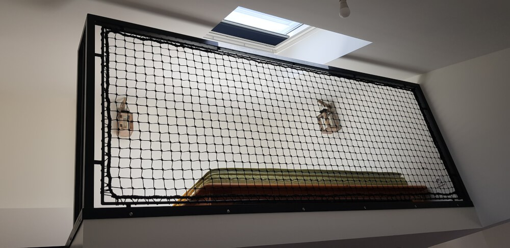 Filet garde-corps installé sur balustrade de mezzanine