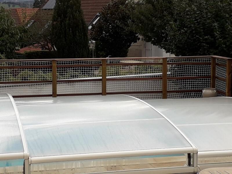 Filet de sécurité blanc entourant piscine couverte