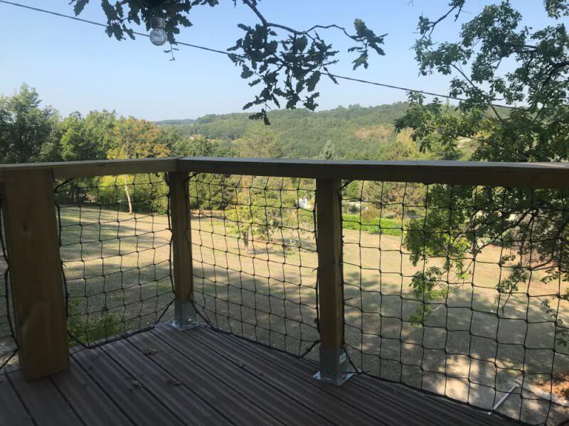 Filet à mailles larges installé sur balcon d'une cabane