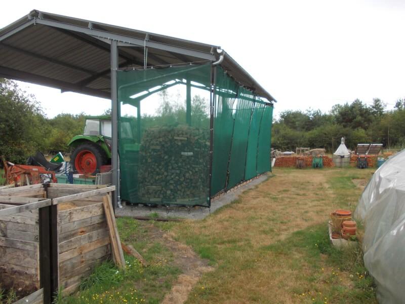 Installation avec filets brise-vent pour protéger le bois de chauffage.