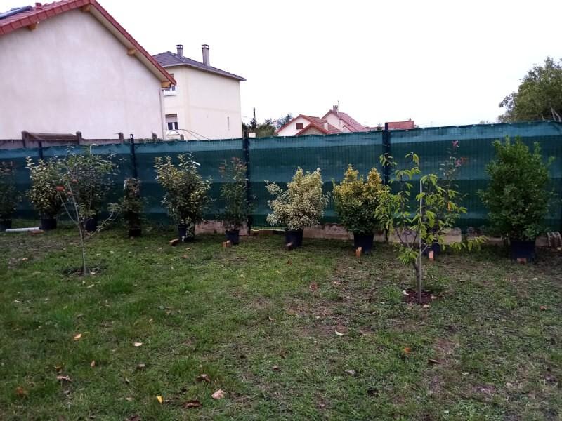 Filet brise-vue vert posé sur un grillage de jardin