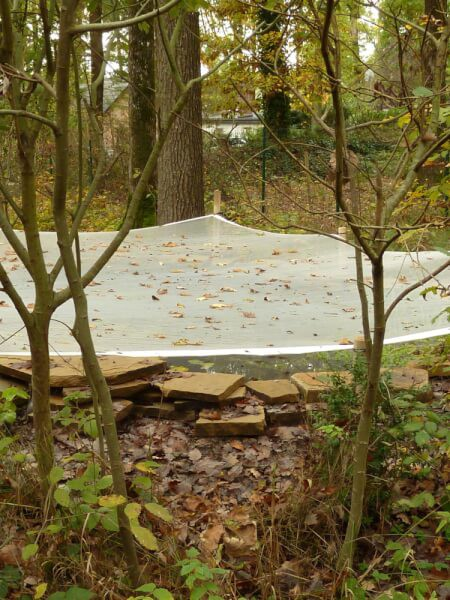 Bassin en forêt protégé par un filet anti-feuilles sur-mesure