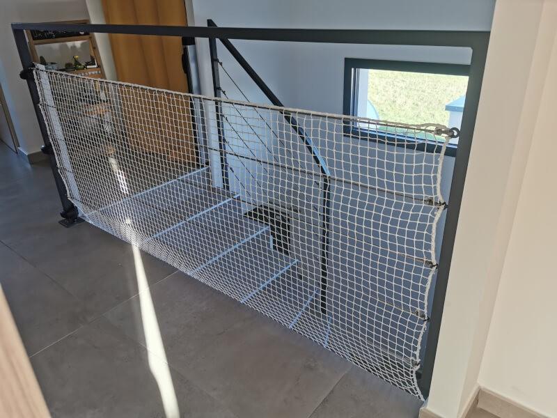Filet de protection enfants posé sur garde-corps escalier en métal