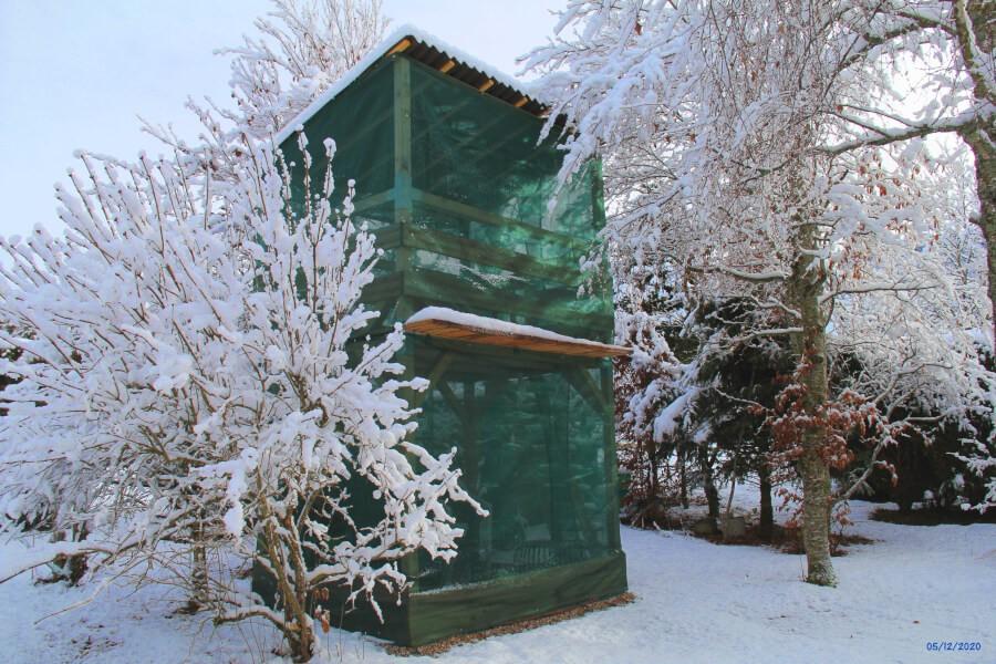 Cabane pour enfants entourée de 2 filets qui protègent totalement de la neige
