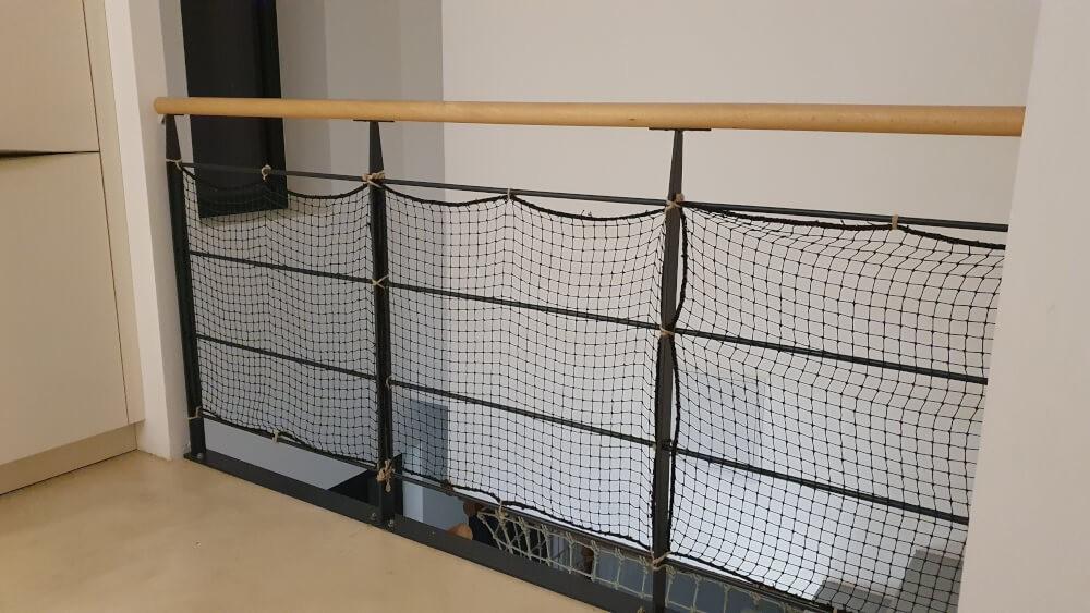 Filet de protection enfants installé sur garde-corps métallique escalier