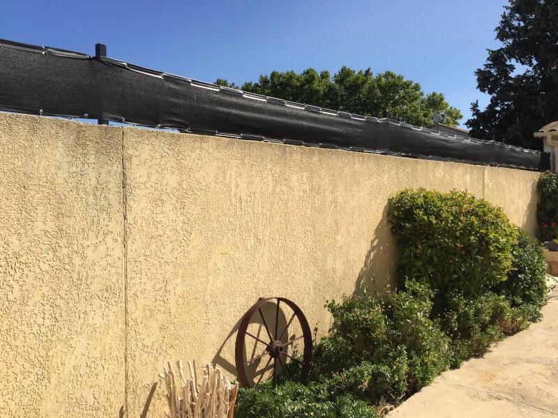 Filet brise-vue sur mur en pierre