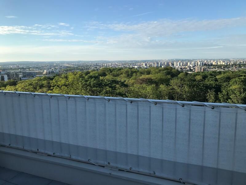 Filet brise-vue blanc installé sur un balcon d'appartement