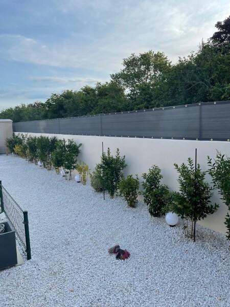 Filet brise-vue de couleur installé sur muret jardin