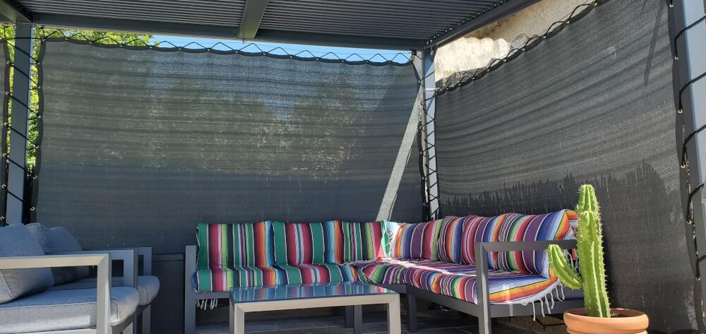 Pose de filets brise vue sur une pergolas bioclimatique maintenu avec filins de bateau inox et Sandow.